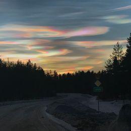 färgade molnformationer ovanför mörk bilväg med skog