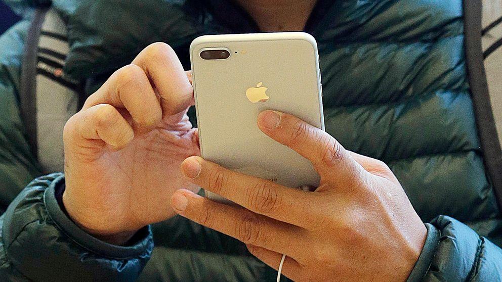 En man knappar på sin Iphone.