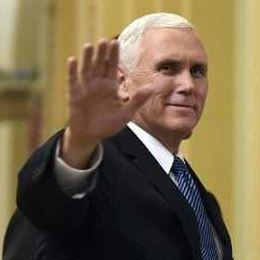 Pence tittar rakt in i kameran. Ler och håller upp handen. Han har vitt kort hår.
