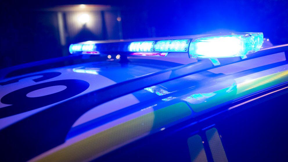 En polisbil i mörkret med blinkande blåljus