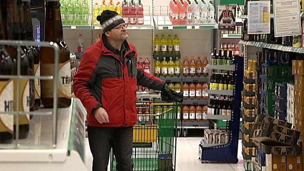 En som som tittar på alkohol i en matvarubutik.
