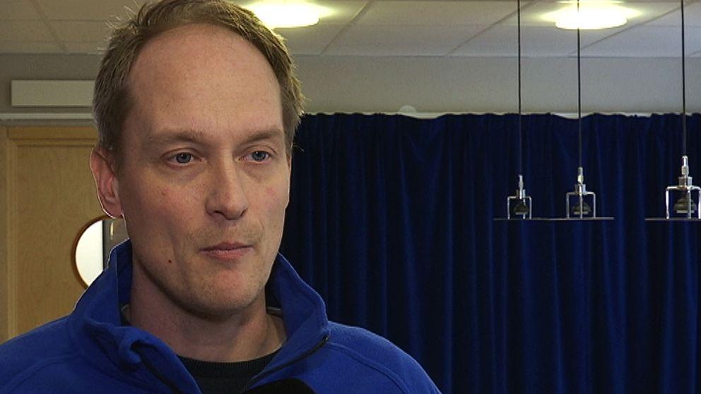 Glenn Olsson, iklädd en blå tröja tittar snett förbi kameran