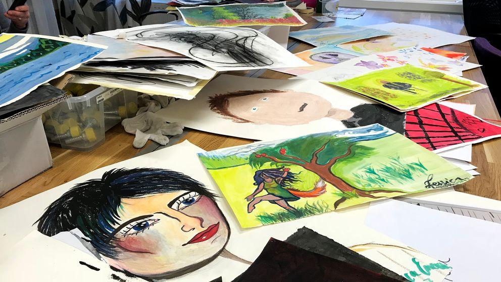 Ett bord täckt av målningar. Närmast syns en målning av ett ansikte och en målning av en person bredvid ett träd