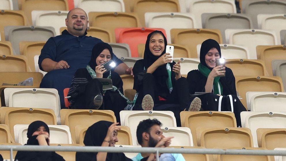 En familj med tre kvinnor och en man sitter på läktaren vid en fotbollsmatch i Saudiarabien.