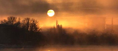 Kall soluppgång i dimma och is.