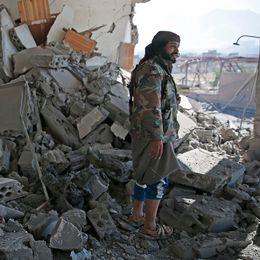 En man inspekterar en raserad byggnad efter ett flyganfall i Sanaa.