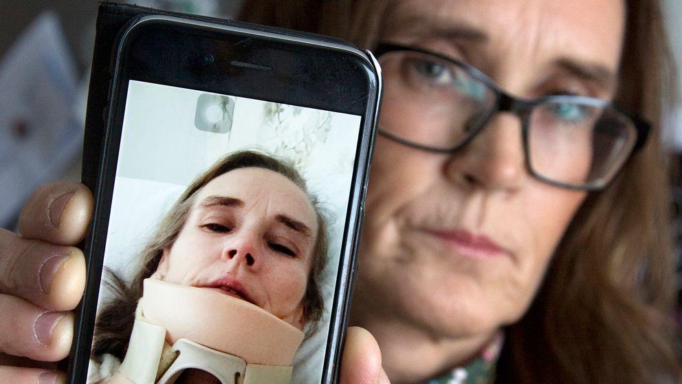 medelålders kvinna håller fram mobil för att visa bild på sig själv med nackkrage