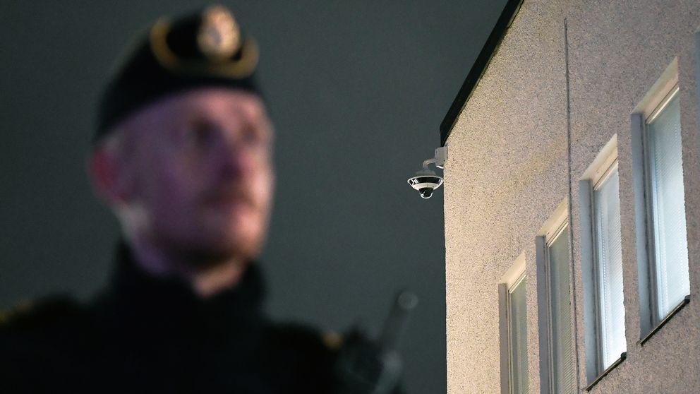 En övervakningskamera på Rinkeby torg och en polis i oskärpa