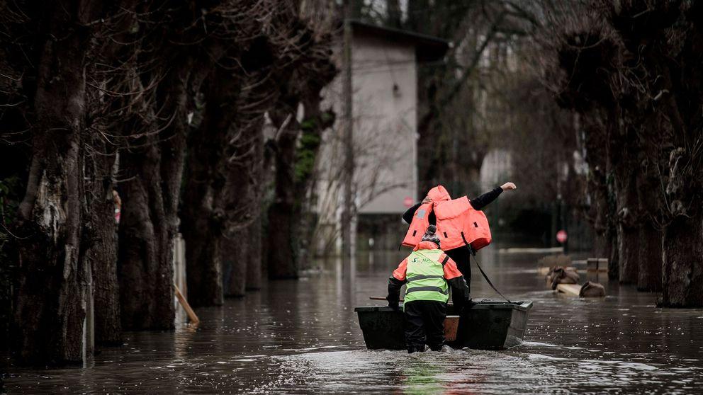 Två personer tar sig fram med båt på en översvämmad gata.