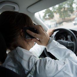 Kvinna talar i mobiltelefon i bil.