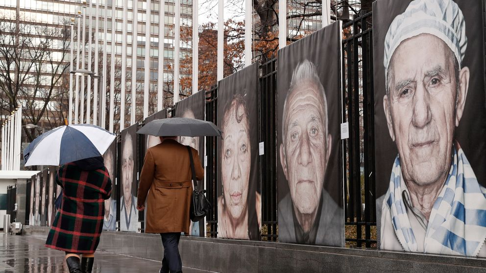 """Umbrella-toting pedestrians pass Luigi Toscano's larger-than-life sized photographic portraits of Holocaust survivors, Tuesday, Jan. 23, 2018, outside United Nations headquarters in New York. Toscano's pictures are part of a two-part exhibit at the UN entitled """"Survivors, Victims and Perpetrators,"""" in conjunction with the Lest We Forget project, commemorating Holocaust victims and survivors. The UN exhibition has two parts: one section focuses on the 1942 Wannsee Conference, its participants and Nazi persecution policies leading to deportations of European Jews and their subsequent murder. The other part features Toscano's portraits of Holocaust survivors living in Germany, the United States, Ukraine, Israel and Russia, sharing their personal stories. (AP Photo/Kathy Willens)"""