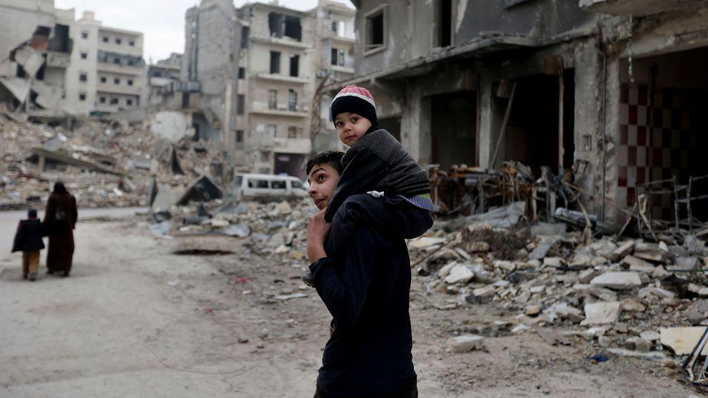 En ung man med ett barn sittandes på axlarna ser sig omkring i en sönderbombad del av syriska staden Aleppo.