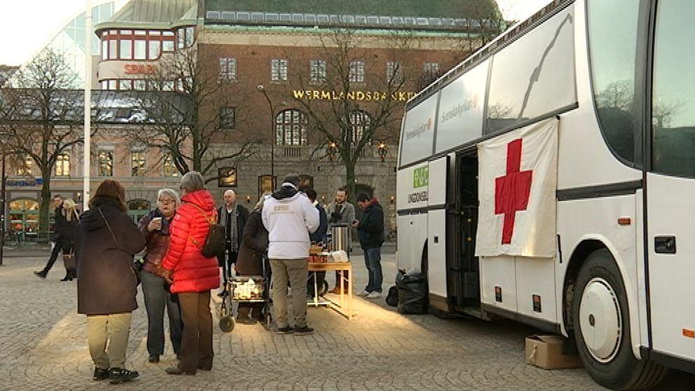 En vit buss med rött kors med en utställning i, på Stora torget i Karlstad.