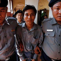 Kyaw Soe Oo har handfängsel på sig och går mellan två poliser som håller i hans armar.