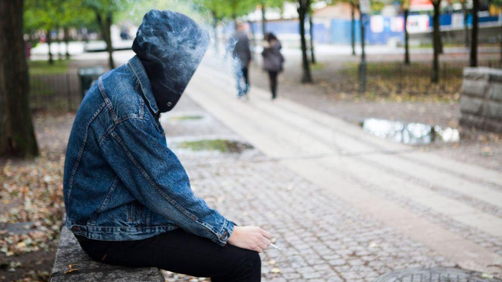 En ung person sitter på en bänk och röker
