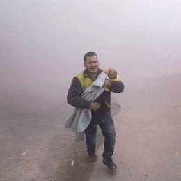En man tillhörande Vita hjälmarna bär sin skadade son när han flyr från ett flyganfall på tisdagen.