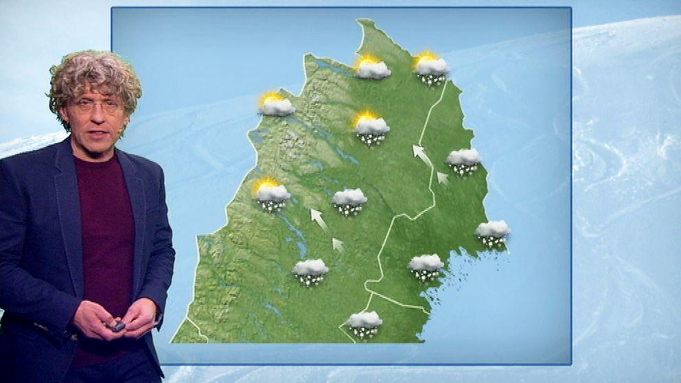 Meteorolog står framför väderkarta