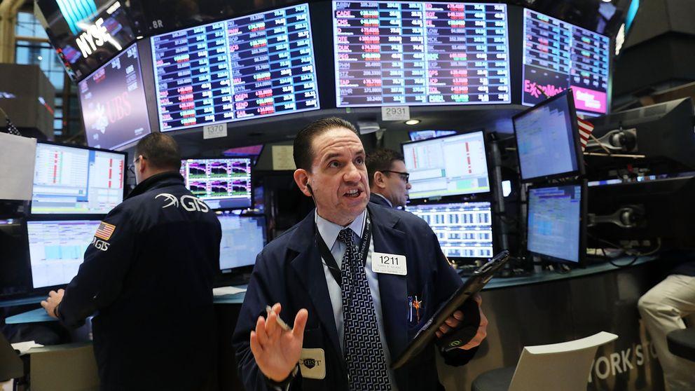 En börsmäklare i kostym står framför ett antal skärmar med börsinformation.