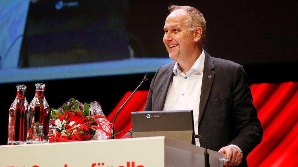 En leende Jonas Sjöstedt vid talarstolen på Vänsterpartiets kongress. På talarstolen har han lagt sin bukett med blommor.