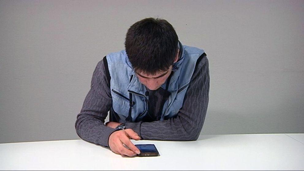 Izatolla tittar på en mobiltelefon.
