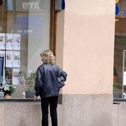 En kvinna tittar på bostadsannonser i ett skyltfönster utanför en mäklarfirma.