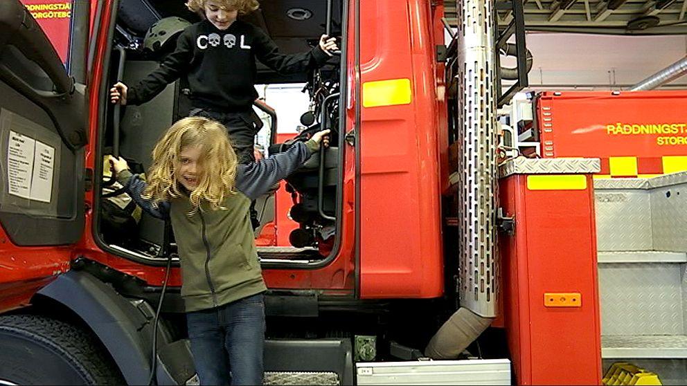 Två barn hoppar ner från förarsätet på en brandbil.