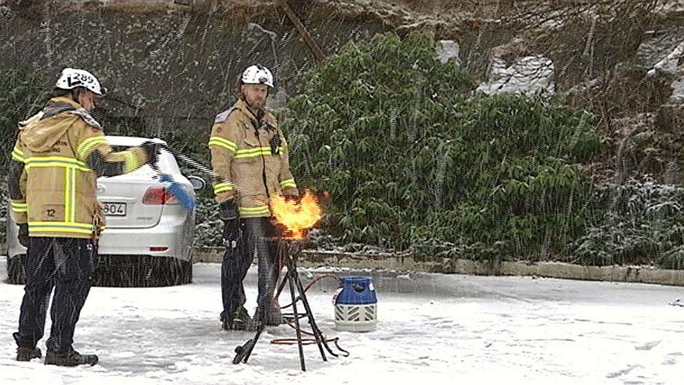 Två brandmän demonstrerar hur en brand i en kastrull ska släckas.
