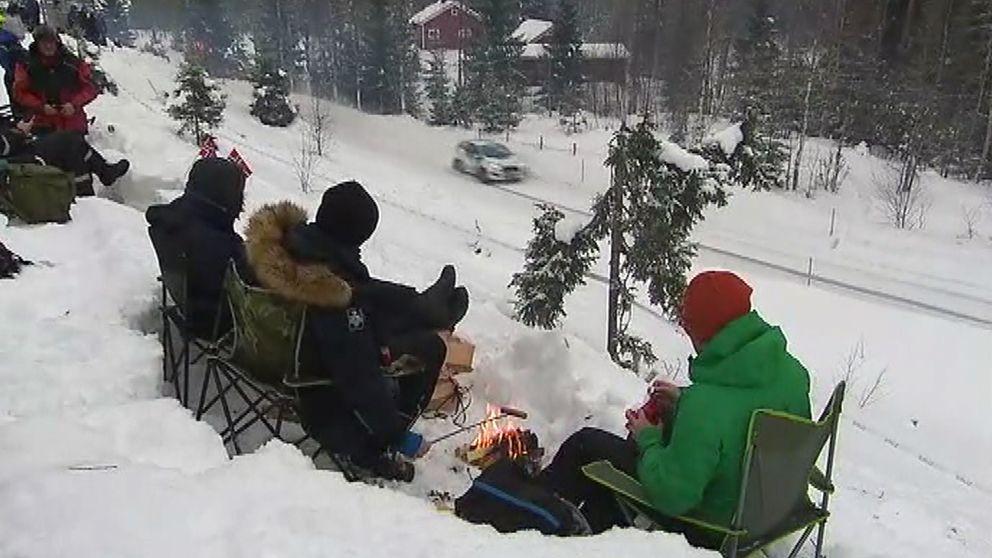 publik som sitter i snön och tittar på rallybil