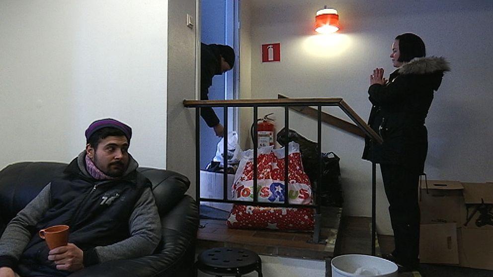 En man sitter i en soffa och håller i en kopp. En kvinna står vid en dörr i bakgrunden