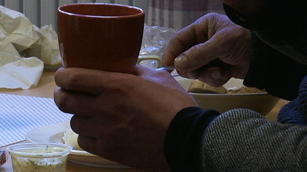 Två händer, den ena håller i en kopp