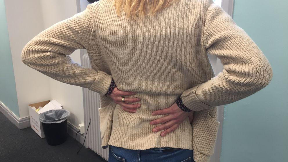 En kvinna tar sig på ryggen då hon känner smärtan av njursvikt.