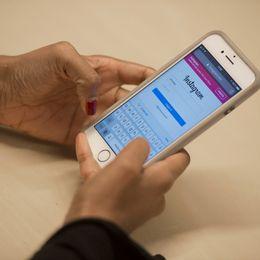 Kvinna håller i mobiltelefon