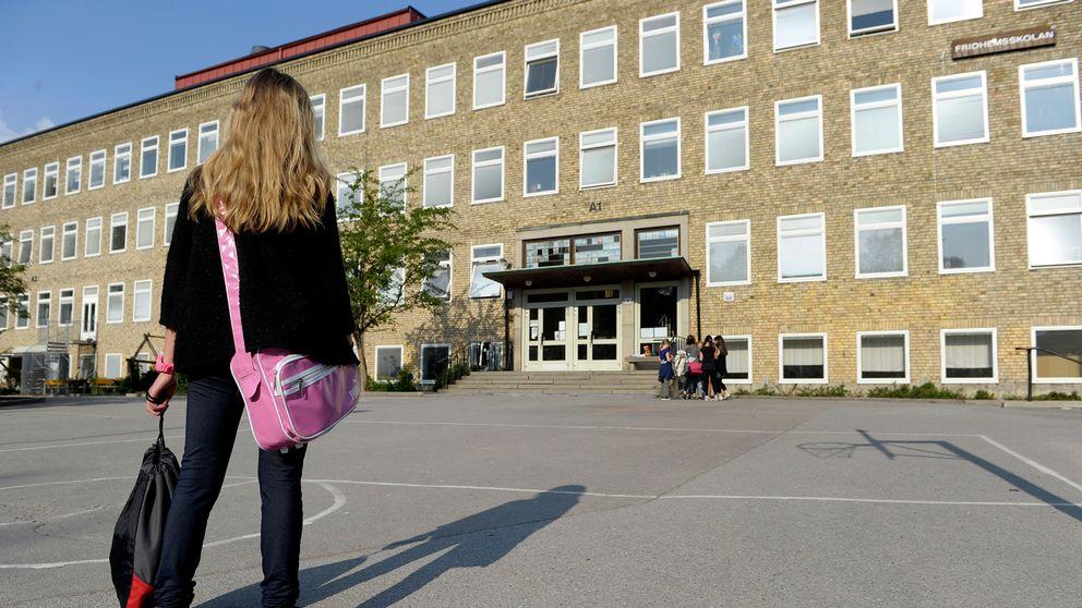 En ensam flicka på väg till skolan över en tom skolgård där en grupp flickor står vid ingången till skolbyggnaden