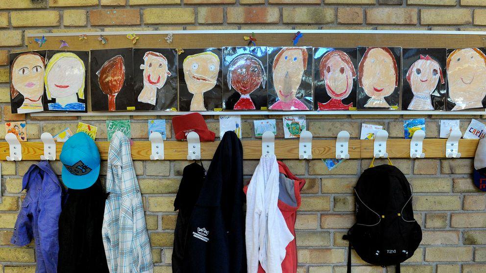 Skolkorridor utanför ett klassrum med kläder på klädhängare och tecknade porträtt av eleverna