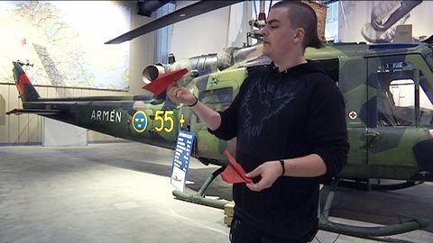 en kille med pappersflygplan framför en helikopter på museum