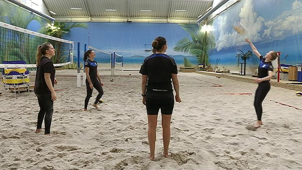 Fyra volleybollspelare tränar i en sandig inomhushall.