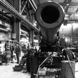 En svartvit bild på en kanon på ett industrigolv. Bredvid står och sitter en grupp med arbetare.