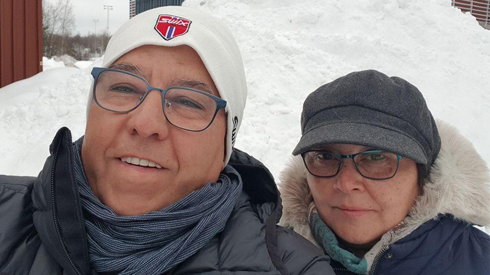 En bild på en man och en kvinna framför en snöhög.