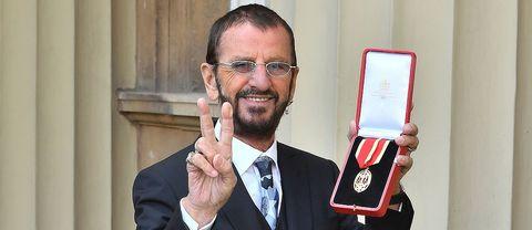 Ringo Starr håller upp sin medalj utanför kungliga slottet i London, England.