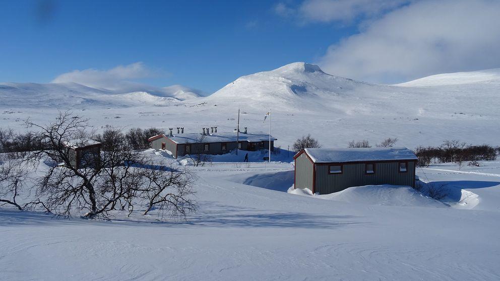 fjällstation i snötäckt fjällvvy och solsken