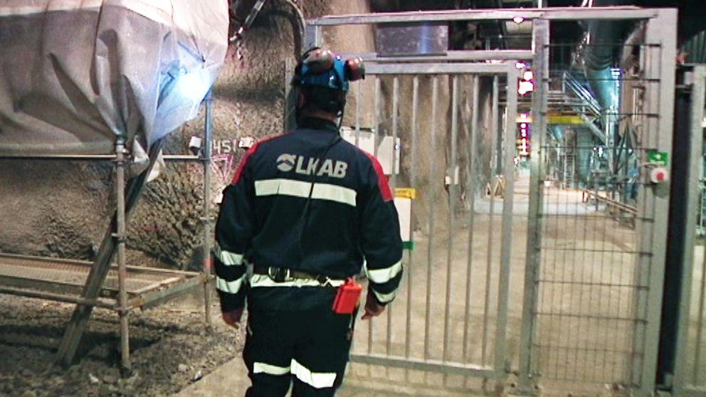 En man i arbetskläder står utanför en grind nere i en gruva.