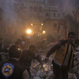 Hjälparbetare från organisationen Vita hjälmarna söker efter överlevande efter ett flyganfall mot den rebellkontrollerade staden Harem i nordvästra Syrien.