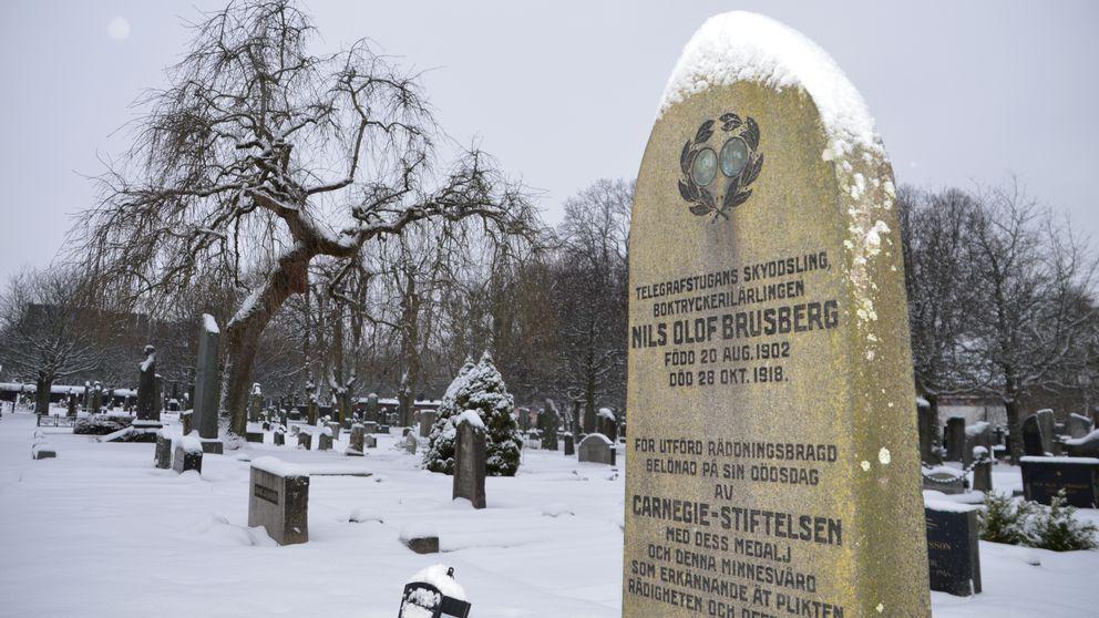 """En gravsten med snö på toppen. I bakgrunden syns ett mörkt träd och en kyrkogård. På gravstenen kan man se en medalj, både fram- och baksida, i en inhuggen lagerkrans. På stenen står det: """"Telegrafstugans skyddsling, boktryckerilärlingen Nils Olof Brusberg. Född 20 aug 1902. Död 28 okt 1918."""""""