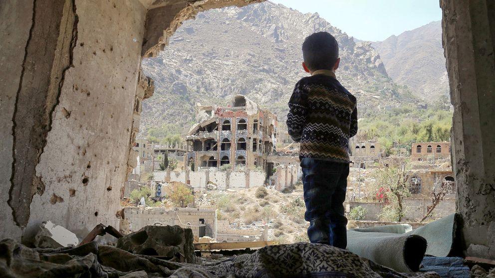 En pojke tittar ut på sönderbombade hus efter ett flyganfall mot staden Taez i södra Yemen.