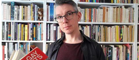 Bibliotekarien Olov Kriström med en av bibliotekets böcker.