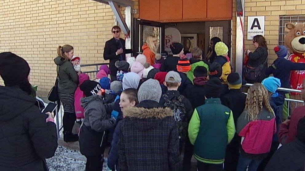 Elever som går in genom en dörröppning.