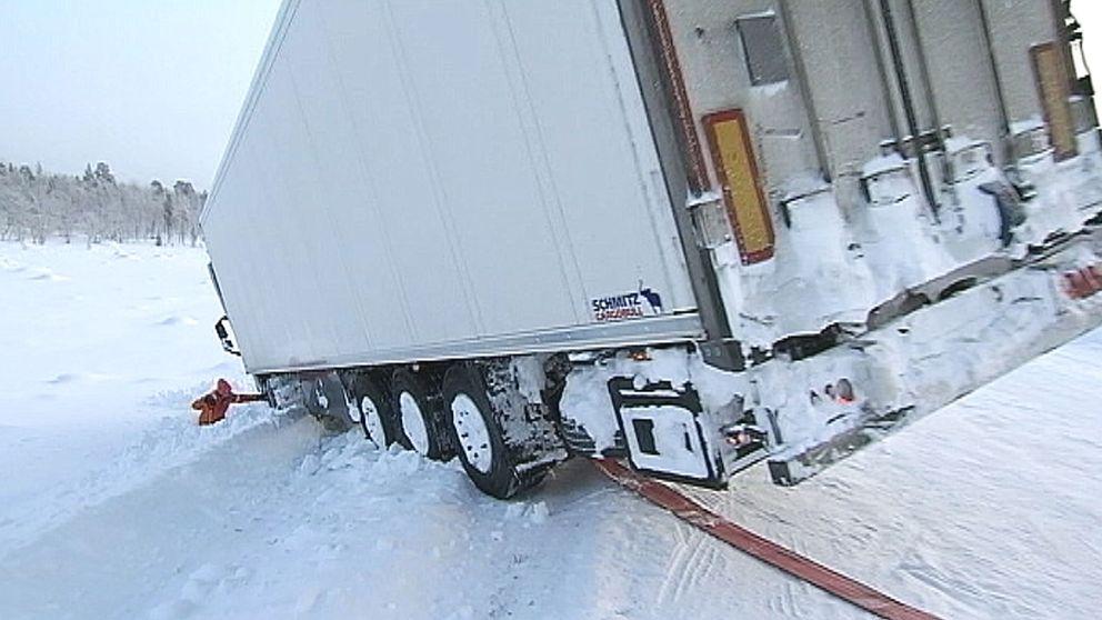 lastbilssläp som står halvvägs ner i diket på vinterväg