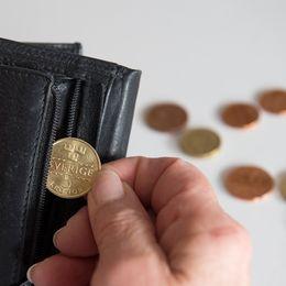 Svensk 5-krona plockas ut ur en svart plånbok