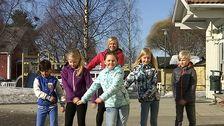 fem barn och en vuxen i en dansrörelse på skolgård