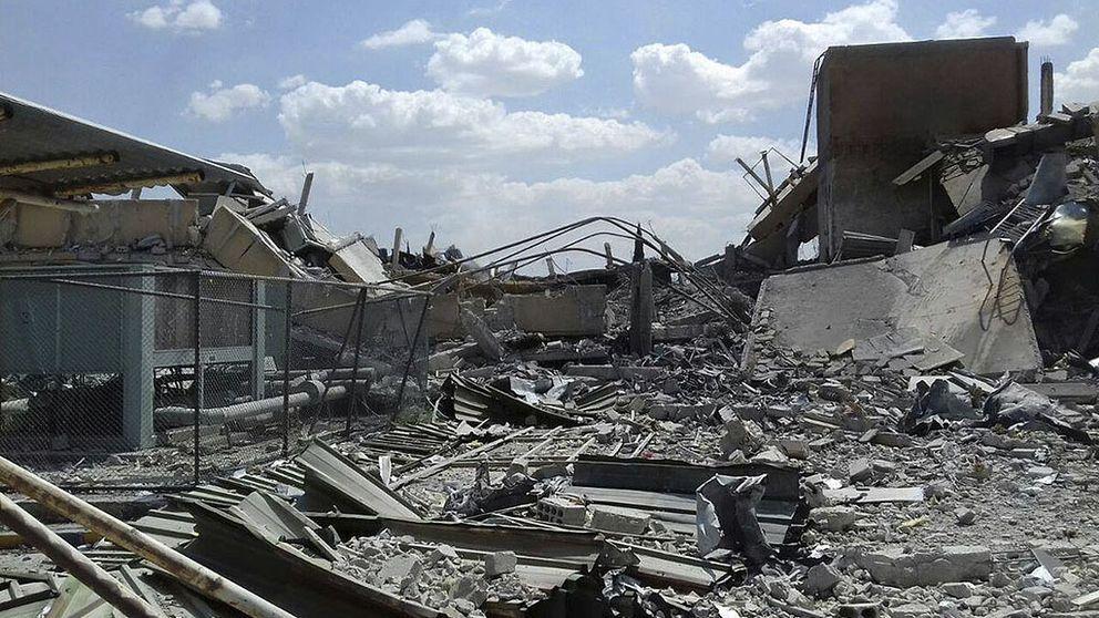 Förstörda byggnader, damm och bråte.